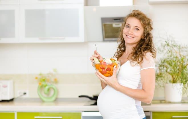 Беременная женщина кушает фрукты
