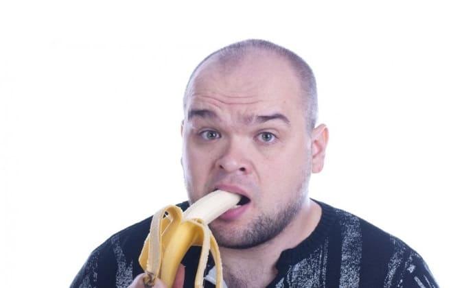Мужчина кушает банан
